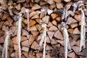 Detail, wedding, pile of wood, logs decorated with small bouquets of flowers