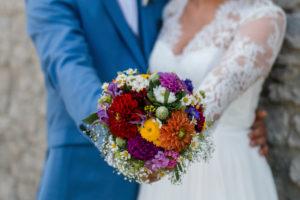 Detailaufnahme, Hochzeit, Brautpaar hält Blumenstrauß in Kamera