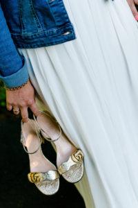 Detailaufnahme, Hochzeit, Braut, lässig mit Jeansjacke und Schuhen in Hand