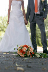 Detail shot, wedding, bridal couple, bouquet of flowers in focus