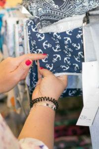 Detailaufnahme von Stoffen bei einem Nähworkshop, Frau wählt Stoff mit Anker aus