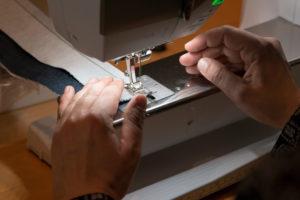 Detailaufnahme von Frauenhand an Nähmaschine bei Nähworkshop mit Stoffmuster
