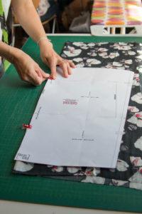 Detailaufnahme von Stoffen bei einem Nähworkshop Frau beim Zuschneiden von Stoff