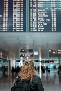Junge blonde Frau am Flughafen München mit Mund-Nasen-Maske / Corona-Reise / Fluggast mit Schutzmaske
