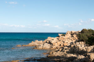 Rocks, cliffs, bay near Orosei in Sardinia with pine trees and blue sea