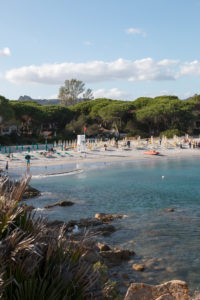Beach section in Sardinia, private beach of a hotel complex with deck chairs and tourists