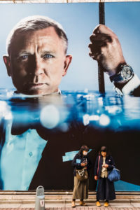 Japan, Honshu, Tokyo, Ginza, Women in front of Daniel Craig Poster Advertising Omega Watches