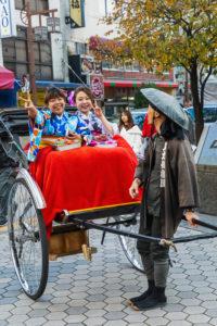 Japan, Honshu, Tokyo, Asakusa, Two Young Women Dressed in Kimono Riding in Rickshaw