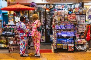Japan, Honshu, Tokyo, Asakusa, Two Woman Dressed in Kimono in front of  Souvenir Shop