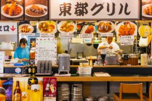 Japan, Honshu, Tokyo, Tsukiji, Tsukiji Outer Market, Seafood Restaurant with Customers Sitting at the Counter