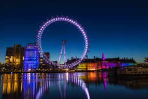 England, London, London Eye and County Hall Building at Night