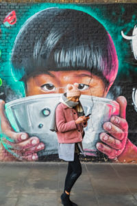 England, London, Southwark, Clink Street, Girl Texting While Walking Past Wall Mural Street Art depicting Asian Child Eating from Bowl