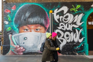 England, London, Southwark, Clink Street, Two Girls Walking Past Wall Mural Street Art depicting Asian Child Eating from Bowl