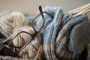 Spectacles and yarns of wool in craft basket