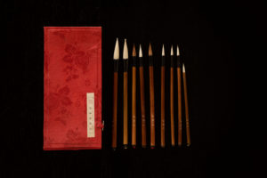 Chinese brush set with red brushes storage box on a black background