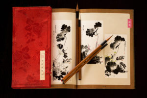 Chinese paint brushes with beautiful Chinese Art book on a black background