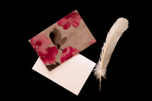 Feather pen white writing paper and flowery envelope on a black background