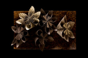 Origami flowers with wooden tray on a black background