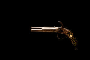 An antique gun, decorative object, on a black background