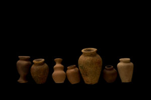 Earthen jars in a row on a black background
