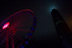 Beleuchtetes Riesenrad neben Wolkenkratzer bei Nacht im Hafen von Hongkong