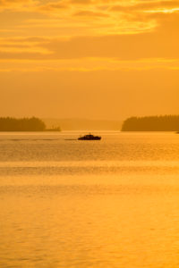 Boat silhouette against the horizon, sunset colors, Finland