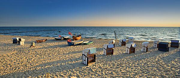 Deutschland, Mecklenburg-Vorpommern, Insel Usedom, Ostseebad Kölpinsee, Strandkörbe und Fischerboote am Strand im Morgenlicht