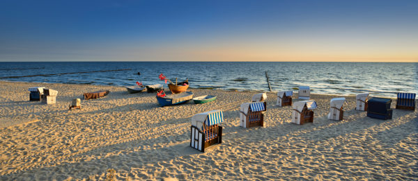 Germany, Mecklenburg-Western Pomerania, Usedom island, Ostseebad Kölpinsee, beach chairs and fishing boats on the beach in the morning light