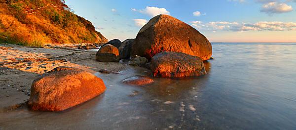 Germany, Mecklenburg-Western Pomerania, Rügen island, Biosphärenreservat Südost-Rügen Mönchgut / Monk's Estates peninsula, Groß Zicker, coastal scenery, coastal forest and boulders, sandy beach, evening light