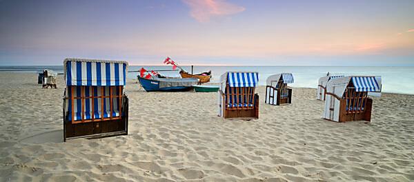 Germany, Mecklenburg-Western Pomerania, Usedom island, Ostseebad Kölpinsee, Usedom island, beach chairs and fishing boats on the beach at sunrise
