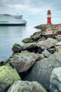 Deutschland, Mecklenburg-Vorpommern, Rostock, Hafeneinfahrt Warnemünde, Ostmole mit rotem Leuchtturm, auslaufende Fähre nach Skandinavien