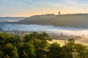 View of Freyburg with Neuenburg Castle, in front the church of Nißmitz, morning fog in the Unstrut valley, Freyburg (Unstrut), Saxony-Anhalt, Germany