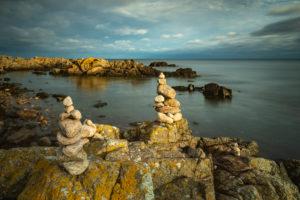 Dänemark, Bornholm, Allinge-Sandvig, felsige Küste mit Steinmännchen im Morgenlicht