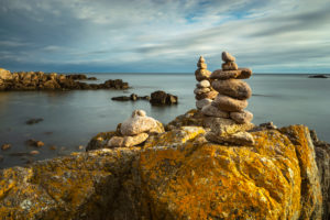 Denmark, Bornholm, Allinge-Sandvig, rocky coast with cairn in the morning light