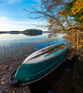 Germany, Brandenburg, Lychen, Quiet evening at the Great Lychensee in autumn, rowboat lies upside down on jetty, colorful foliage