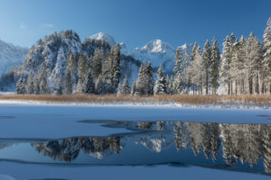 Ameisstein (776 m) mountain at the Lake Almsee in winter. The lake is frozen and snow covered, clear blue sky.