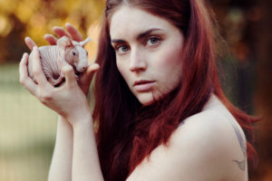Portrait of a young woman with skinny guinea pig