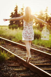 Young woman in dress balancing on a railway track