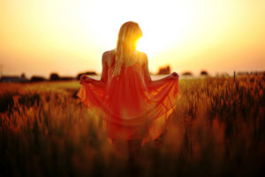 Woman with dress standing in the cornfield at sunset