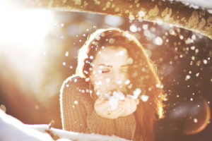 Portrait of a young woman in the snow in backlight