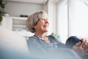 Portrait of laughing senior woman sitting on couch at home
