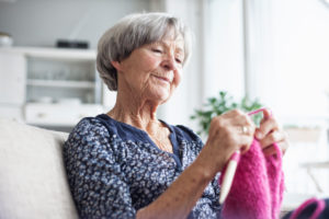 Portrait of knitting senior woman sitting on couch at home