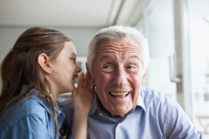 Granddaughter wispering something in the ear of her grandfather