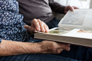 Hands of senior couple holding photo album, close-up