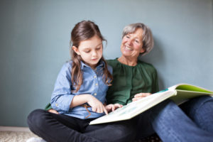 Happy grandmother and her granddaughter sitting on the floor with a book