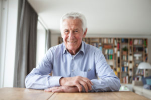 Portrait of confident senior man sitting at table in the living room