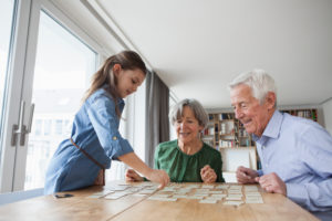Little girl playing memory with her grandparents at home