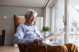 Portrait of senior man sitting on armchair at home reading newspaper