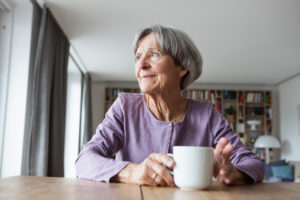 Portrait of senior woman sitting at table with cup of coffee looking through window