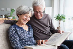 Happy senior couple sitting on the couch of living room watching photo album